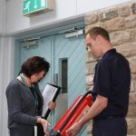 Fire officer showing business owner a fire extinguisher
