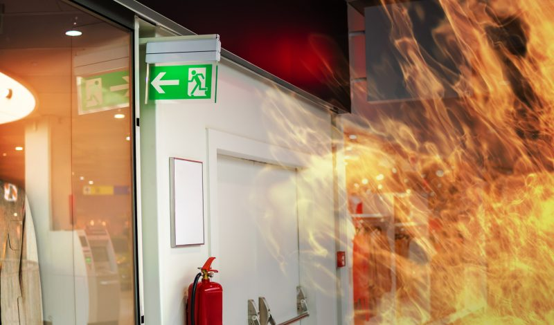 Composited image of an emergency fire exit sign in a shop near to some double doors with push bar exits. Flames can be seen licking the right hand side of the image.