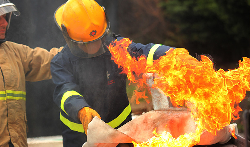 fire cadet using fire blanket on a fire
