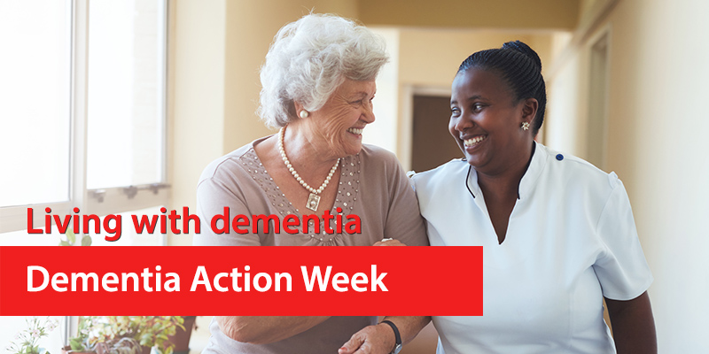 An older lady is walking arm in arm with a carer. They're smiling at each other. Header image for Living with dementia during dementia awareness week