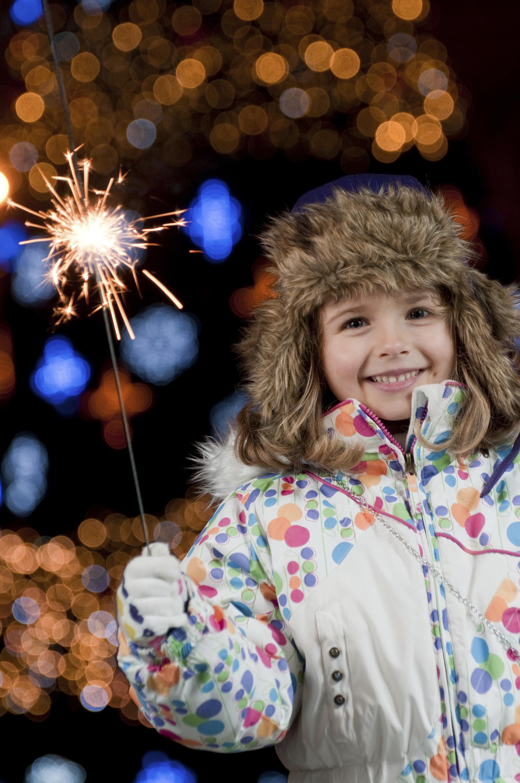 Girl holding sparkler in gloved hand