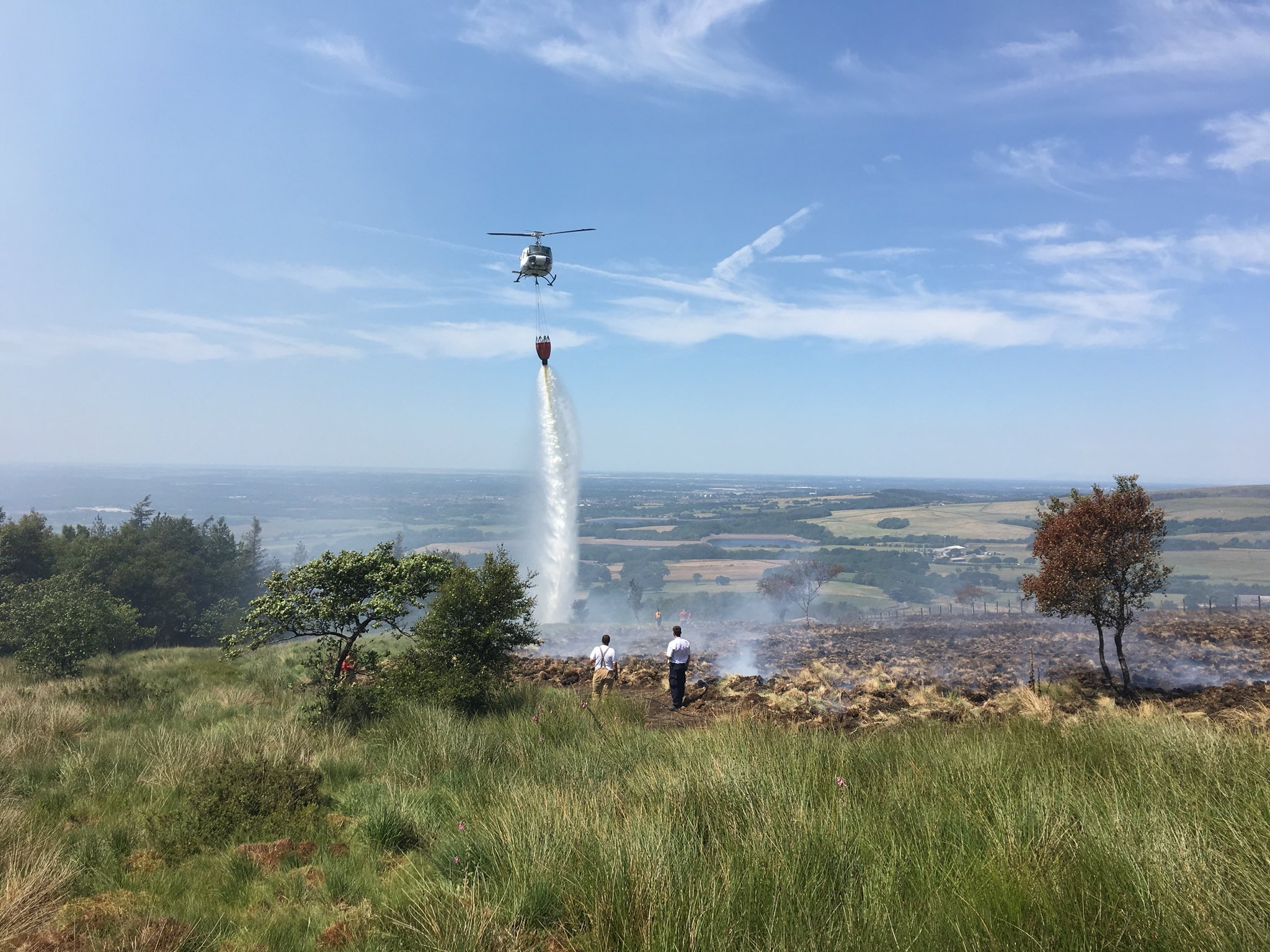 Helicopter dropping water onto moorland on Winter Hill. Two fire officers can be seen just ahead of where the helicopter is.