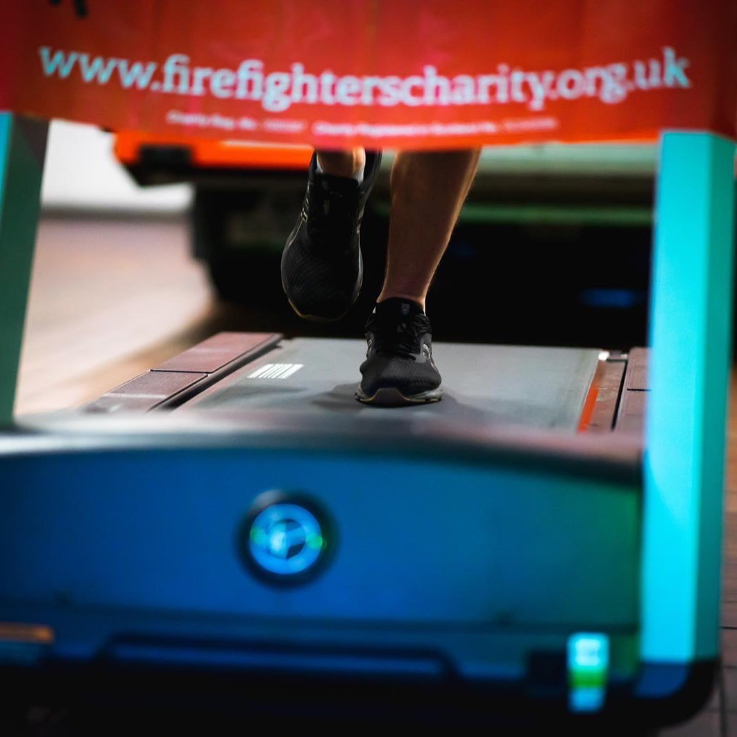 picture of the bottom of a treadmill and some legs running along with a banner of The Fire Fighters charity banner
