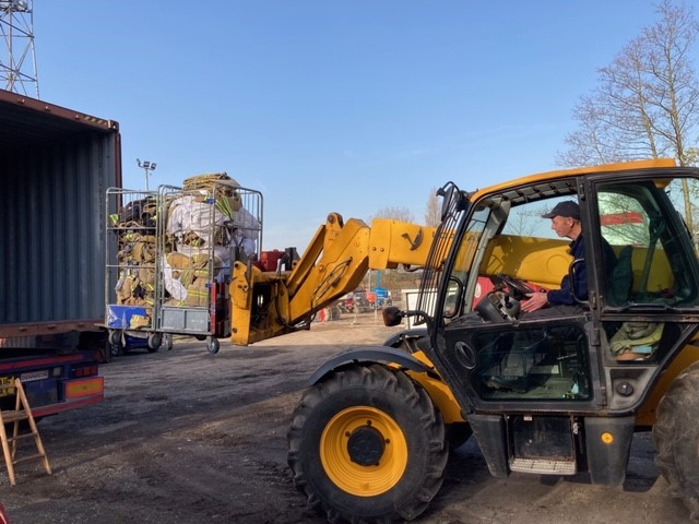 Image of fork lift truck loading a container with personal protective equipment donations